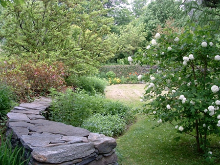 A curving stone wall and perennial gardens.