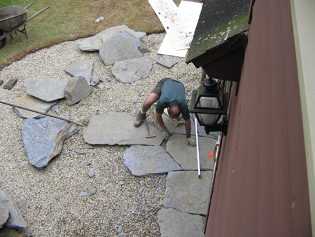 "A Hilltown Tree & Garden crew member fitting the flagstone slabs sourced locally from Goshen, MA on a gravel base 12"" deep."