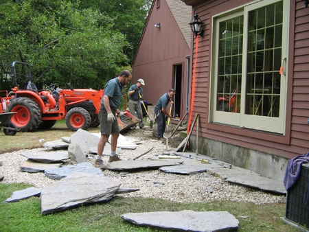 The placement of each flagstone piece of a patio is an art, while making sure it has the appropriate pitch away from the house is a science.
